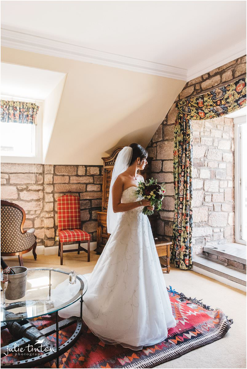 Bride with bouquet on morning of her wedding at Dalhousie Castle