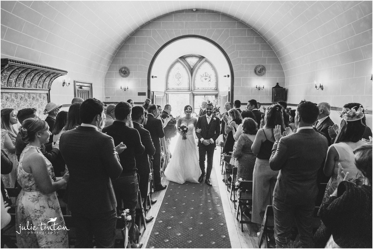 Bride and Groom walking down the aisle at Dalhouse Castle Chapel.