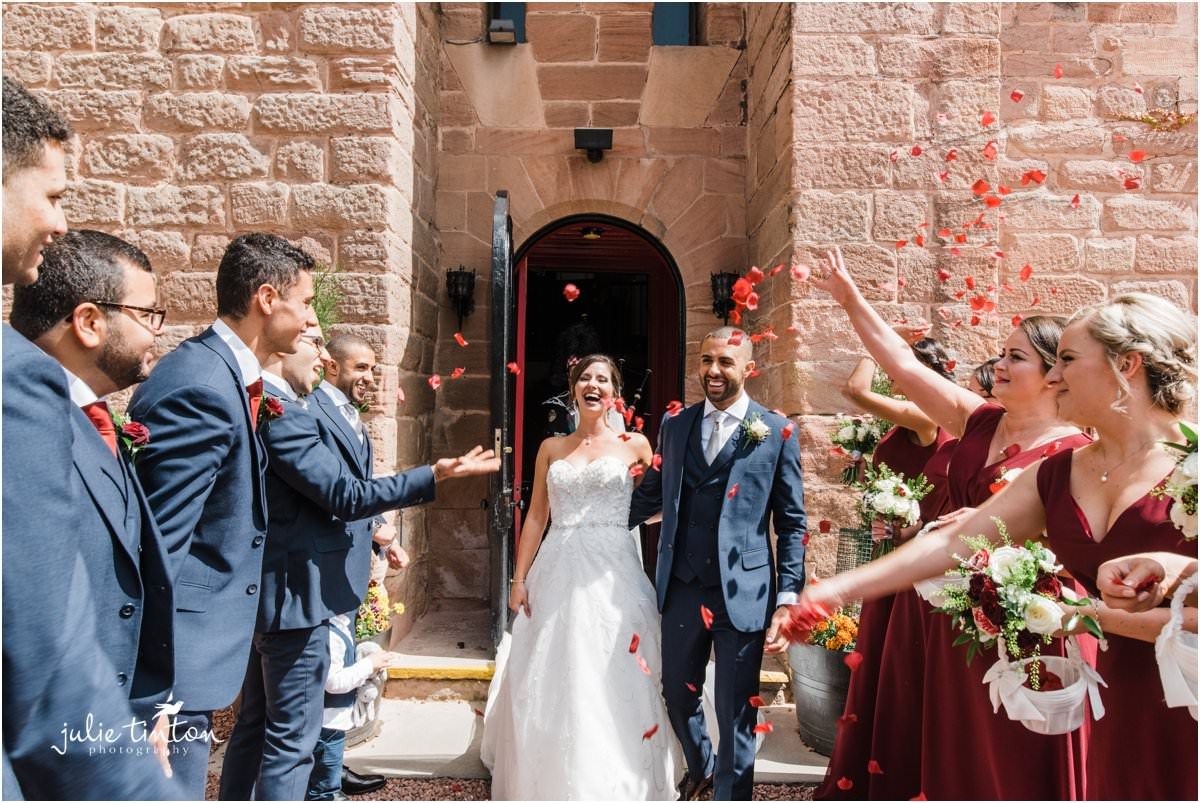 Bride and Groom laughing through red confetti petals from guests at Dalhousie Castle