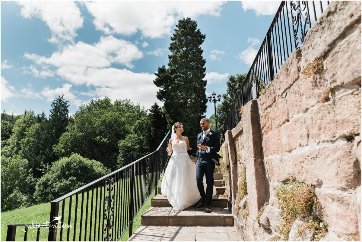 Bride and Groom walking down steps with champagne to meet guests with blue sky in summer
