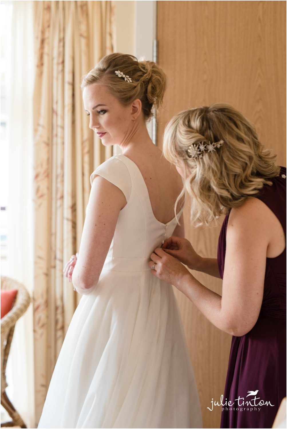 Bridesmaid helping bride to get dressed