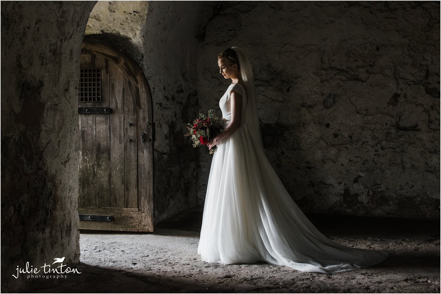 A bride in a doorway with bouquet at Inchcolm Island Abbey
