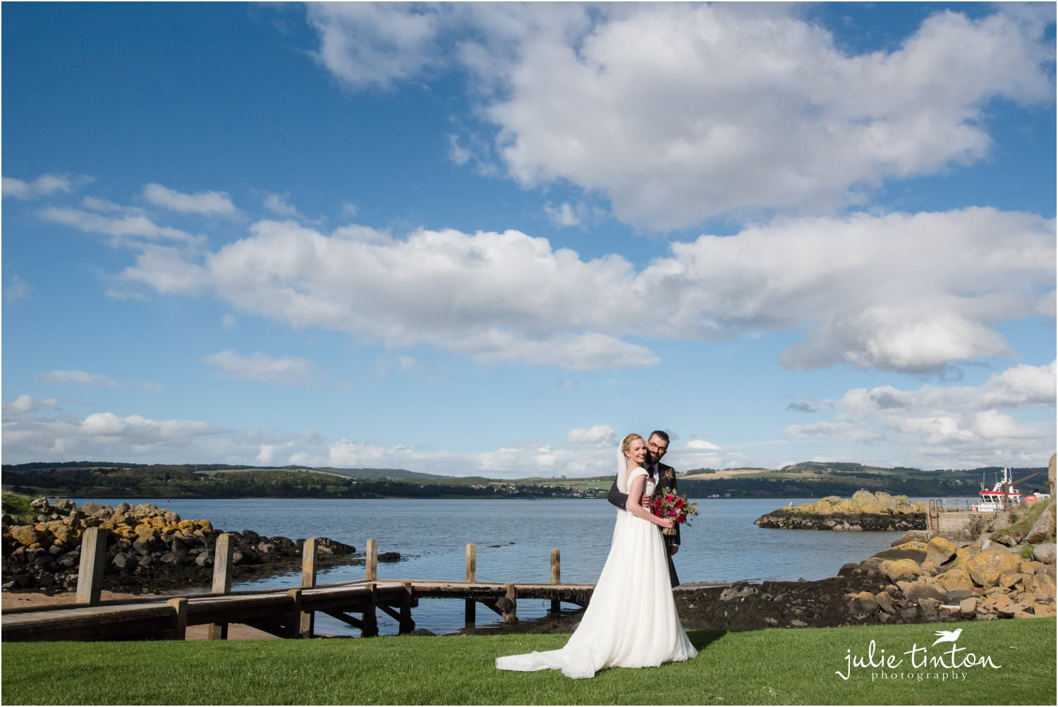 Bride and Groom with blue sky backdrop on Inchcolm Island
