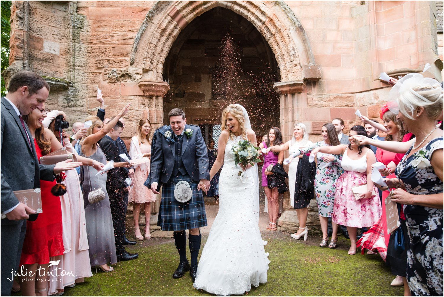 Bride and Groom outside church with confetti throw with guests