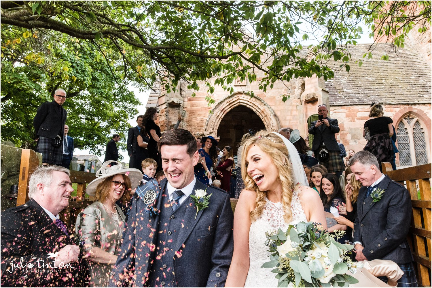 Bride and Groom laughing at confetti at church wedding