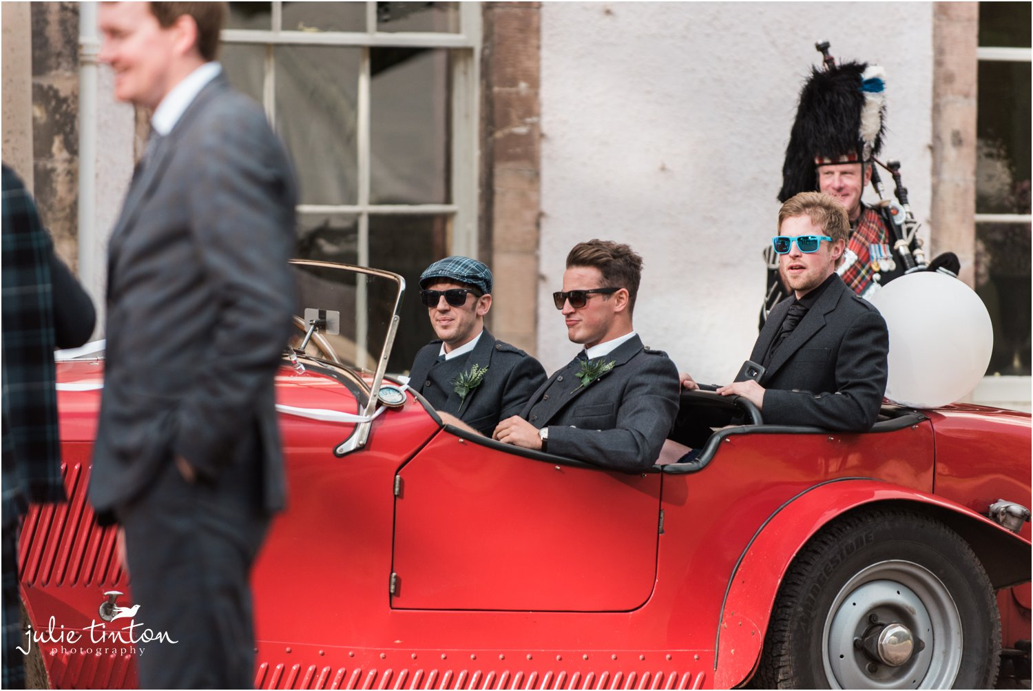 Groomsmen arrive at wedding in classic red car