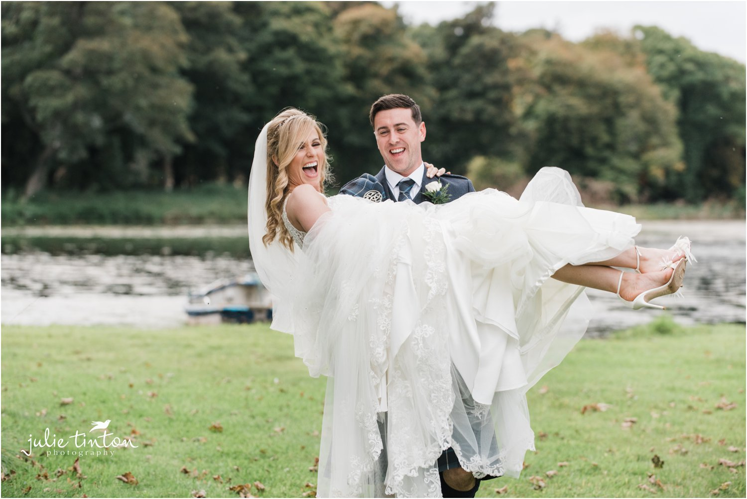 Groom carrying his bride in his arms laughing at Broxmouth Park