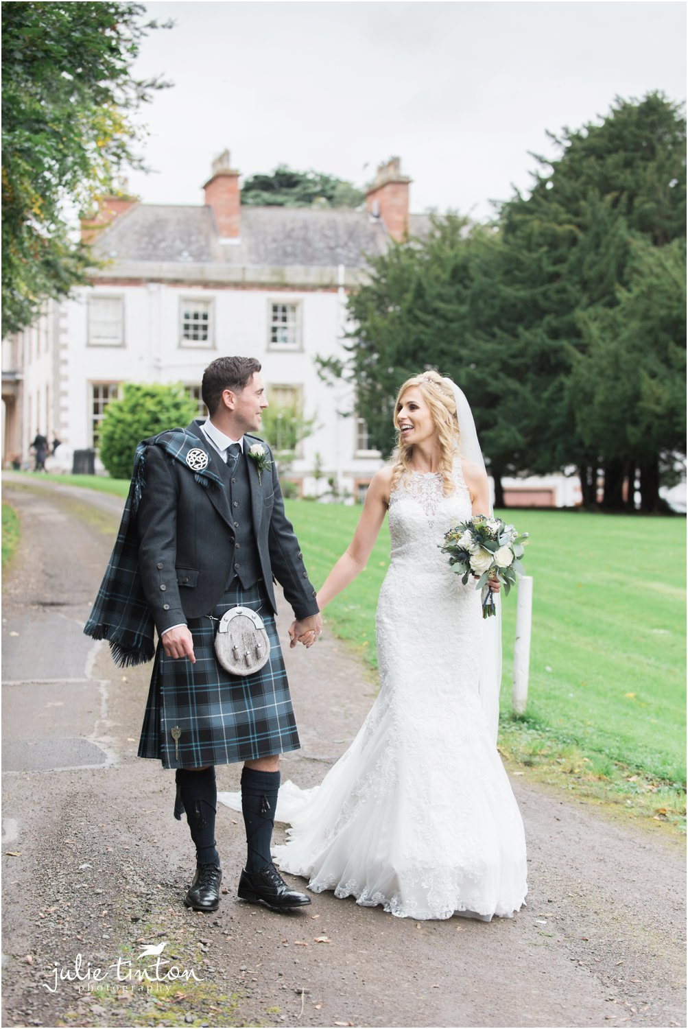 Bride and groom walking with Broxmouth Park House in the background